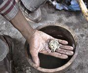 Dans sa main, une richesse. Une fois refroidi, l'or de kéniéba est souvent revendu en plaquettes.