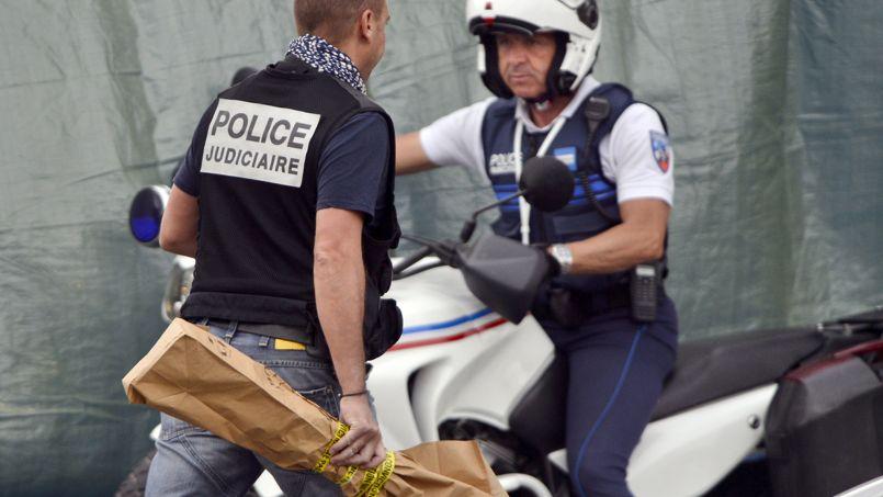 Des policiers transportent des pièces à conviction sur les lieux du crime.