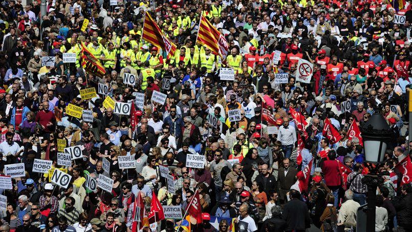 <strong>ESPAGNE -</strong> À Madrid et à Barcelone (photo ci-dessus), les manifestants ont envahi les grandes artères commerciales en brandissant drapeaux et pancartes où l'on pouvait lire: «L'austérité ruine et tue» ou «les réformes sont du vol». Au total, 82 manifestations étaient organisées en Espagne pour «mettre en évidence l'échec total des politiques d'austérité» .«J'ai de la chance parce que j'ai du travail. Mais à la vitesse à laquelle on détruit des emplois en Espagne, je crois que bientôt cela m'arrivera à moi aussi», témoignait José Antonio Sebastian, un ingénieur de 50 ans. «Nous n'avons plus d'autre choix que de partir chercher du travail à l'étranger».
