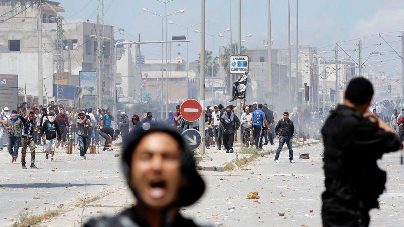 Des policiers anti-émeutes face aux manifestants, dimanche à Tunis.