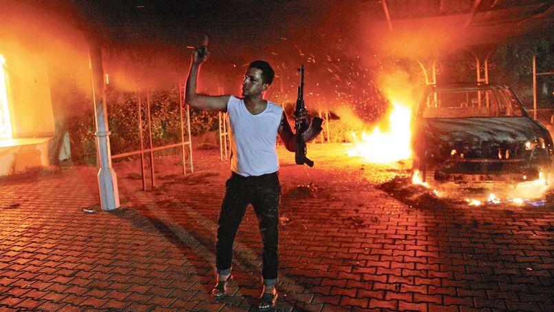 Un homme brandit une arme devant le consulat américain de Benghazi en flammes, le 11septembre 2012 en Libye.