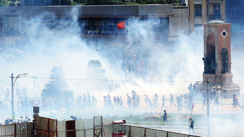 Des manifestants, vendredi sur la place Taksim, dans un nuage de gaz lacrymogènes.