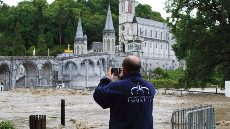 Un gardien du sanctuaire prend, mardi, une photo de la basilique envahie par le débordement du gave de Pau. À Lourdes, les pèlerins et plusieurs hôtels ont dû être évacués devant la violence de la crue