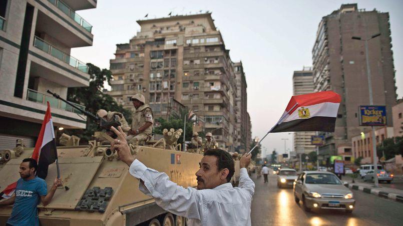 Un tank acclamé par les habitants dans une rue du Caire, mercredi.