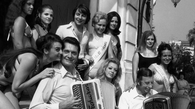 Entourant les accordéonistes André Verchuren (à gauche) et Aimable et le chanteur Monti (au second plan), ces jolies filles sont candidates au titre de reine de la Côte d'Azur au Casino Royale de Nice, le 4 octobre 1969.