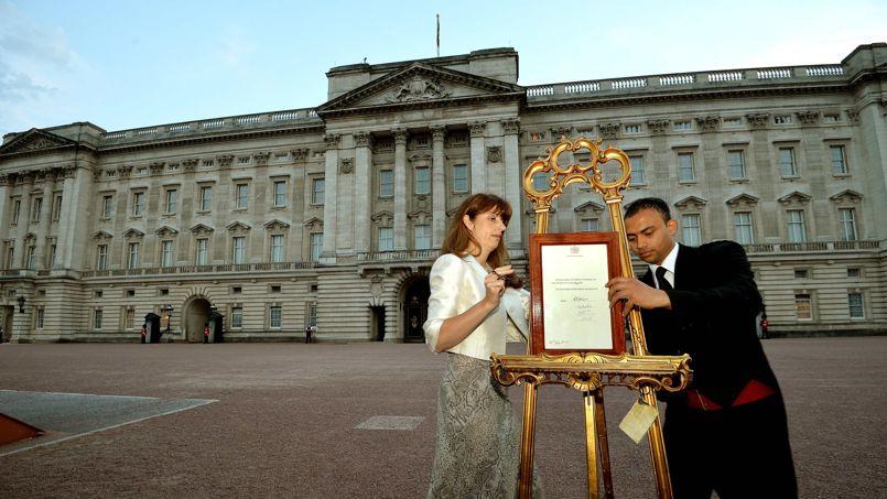 Badra Azim et la secrétaire de la reine Ailsa Anderson installent sur le chevalet l'annonce de la naissance du prince George, le fils de Kate Middleton et du prince William.