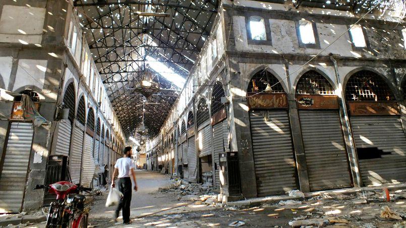 LA SYRIE PLEURE. Il est seul dans le souk historique de Homs, ville stratégique sur la route d'Alep. Comme tant de lieux historiques syriens depuis le début de la guerre, le marché a été déserté, vidé, détruit. Après les bombardements à l'arme chimique sur la banlieue de Damas, à deux heures de route, la violence de la reconquête de cette ville stratégique par l'armée régulière syrienne et le Hezbollah libanais résonne de façon inquiétante. On avait soupçonné l'emploi d'armes chimiques dans cette bataille de Homs dès le mois de janvier dernier. Sans que la communauté internationale réagisse. Les faits se répètent, et la Syrie s'écroule lentement; son histoire disparaît dans la poussière et le fracas des bombes.