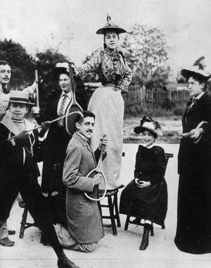 En 1892, Marcel Proust à 21 ans, à genoux et tenant uneraquette de tennis, devant Jeanne Pouquet (la Gilberte de la Recherche) debout sur une chaise.