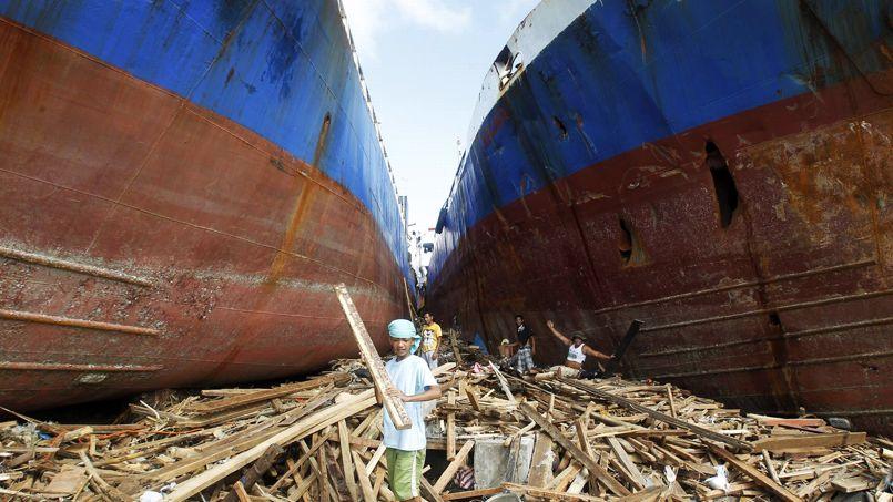 ÉCHOUÉS. Un enfant ramasse des planches de bois entre deux cargos échoués sur la terre ferme après le passage du typhon Haiyan, il y a 4 jours. Ce lundi 11 novembre, les secours américains peinaient à apporter de l'aide au centre des Philippines. «Tout est détruit», a simplement décrit un général américain arrivé sur la ville de Leyte avec quelque 90 Marines et deux avions remplis de vivres et de matériel.