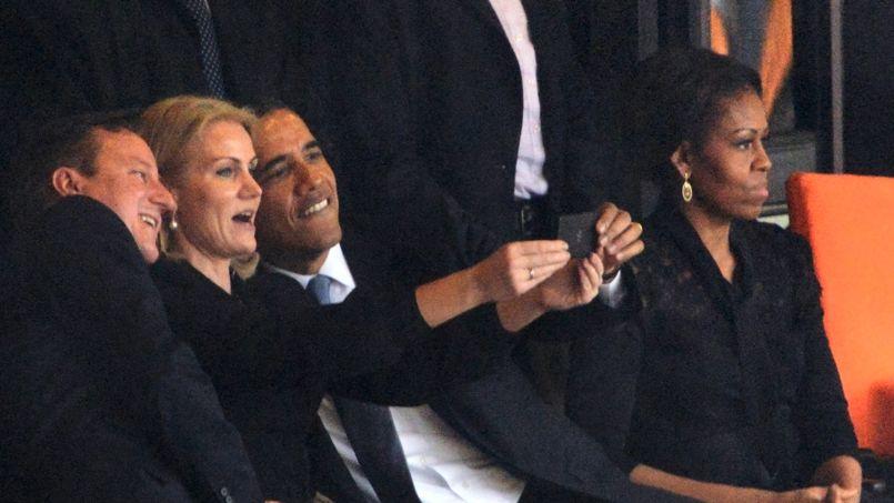 La chef du gouvernement danois propose à Barack Obama et à David Cameron, qui vient de les rejoindre, de poser ensemble sur une même photo. Le président américain l'aide à maintenir son téléphone portable.