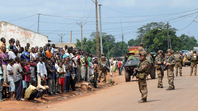La foule observe des soldats français positionnés au nord de Bangui, mardi dans la capitale centrafricaine.