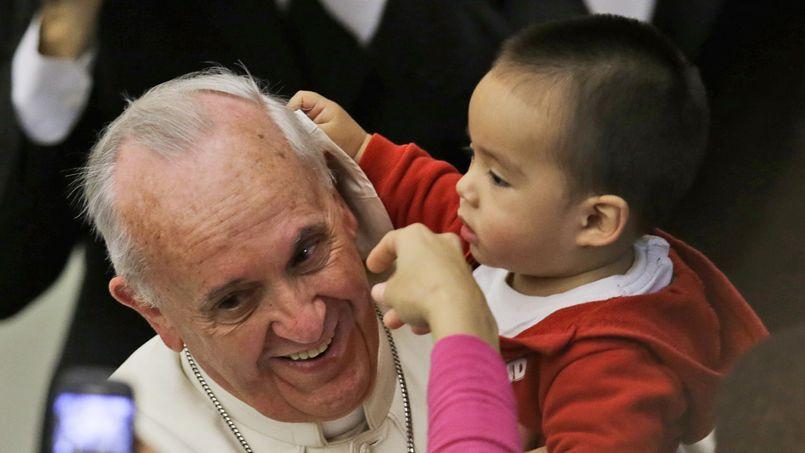 Détendu et souriant, le souverain pontife a laissé le bambin lui passer la main dans les cheveux.