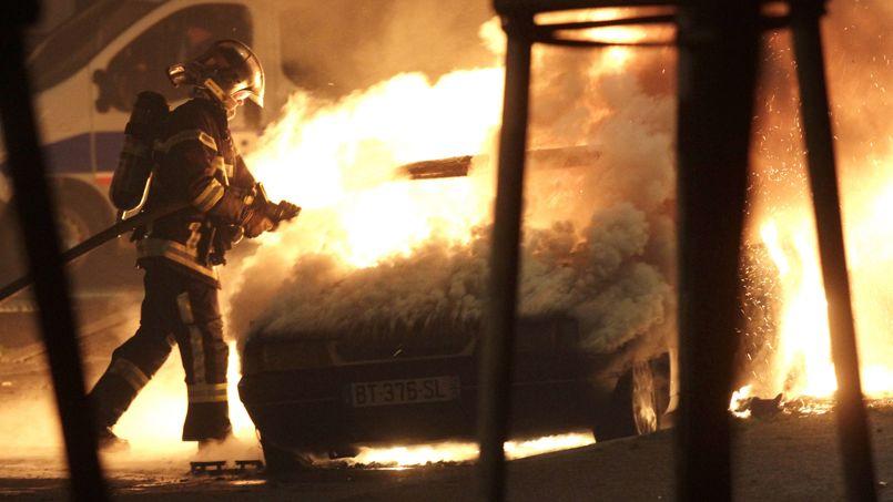 Un pompier intervient sur un incendie de voiture à Strasbourg le soir de la Saint-Sylvestre 2013.