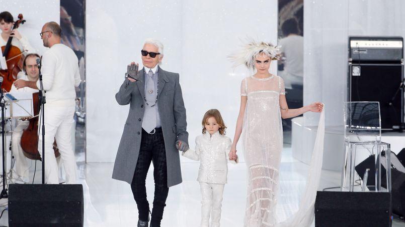 Délicatesse. Ce mardi 21 janvier, Karl Lagerfeld a présenté au Grand Palais, à Paris, sa dernière collection Chanel couture du printemps/été prochain. A la fin du défilé, le créateur est réapparu, accompagné du top britannique Cara Delevingne, habillée en mariée, tout en transparence avec une longue traîne, avec un garçonnet d'honneur de choix: le filleul de Karl, Hudson