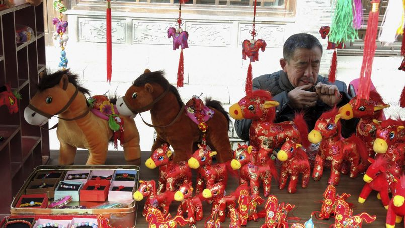 La boutique d'un marchand de souvenirs en train de fabriquer des petits chevaux à Nanjing, dans la province chinoise de Jiangsu, le 19 janvier.