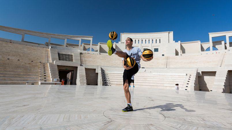 Ce jeune basketteur jongle avec adresse au coeur de l'amphithéatre du Katara Cultural Village.