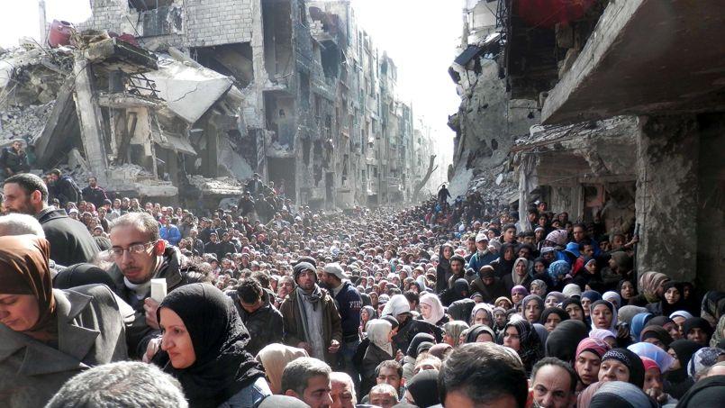 ENFER. Sur cette image, prise le 31 janvier dernier, des membres du camp de réfugiés palestiniens de Yarmouk à Damas, en Syrie, attendent pour recevoir l'aide alimentaire. L'agence de l'ONU en charge de leur sort fait tous les efforts possibles pour leur venir en aide mais les résultats sont maigres: jusqu'à présent, deux convois ont pénétré à Yarmouk ces derniers mois, avec seulement 138 rations de nourriture. En attendant, la famine décime le camp, et les 18.000 habitants subissent un siège impitoyable de la part de l'armée syrienne. Selon l'Observatoire syrien des droits de l'homme, 85 personnes, dont 25 femmes et cinq enfants, sont mortes de faim.