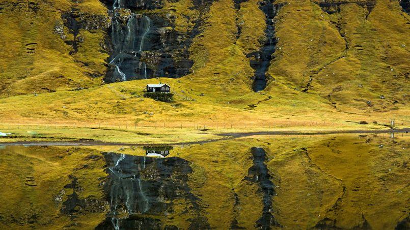 Sur l'île de Végar, la montagne et une cascade se mirent dans les eaux d'un lac. L'une des mille merveilles sur le chemin des randonneurs.