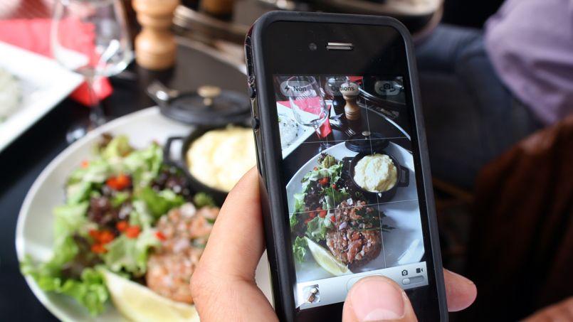 Un individu prend une photo de son plat dans un restaurant parisien. Cette pratique s'appelle le «Foodporn».