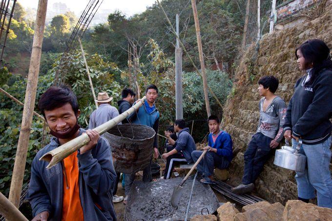 Des membres de la secte habitant le village travaillent bénévolement à la construction des vestiaires du terrain de football.