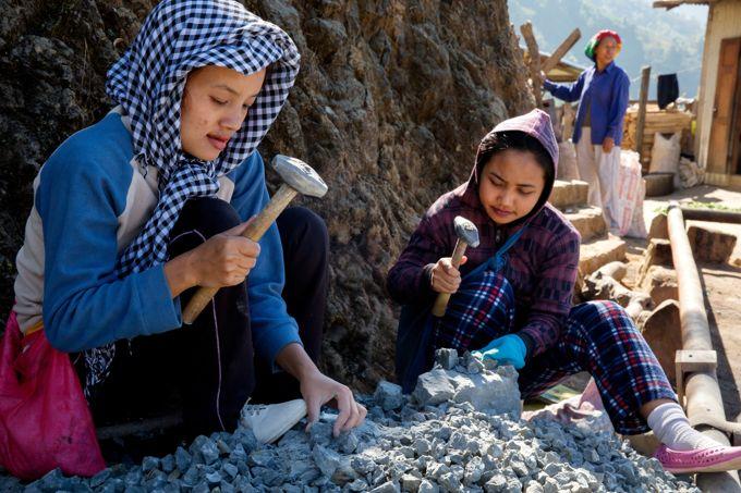 Des jeunes femmes concassent des pierres qui serviront aux travaux de construction dans le village.