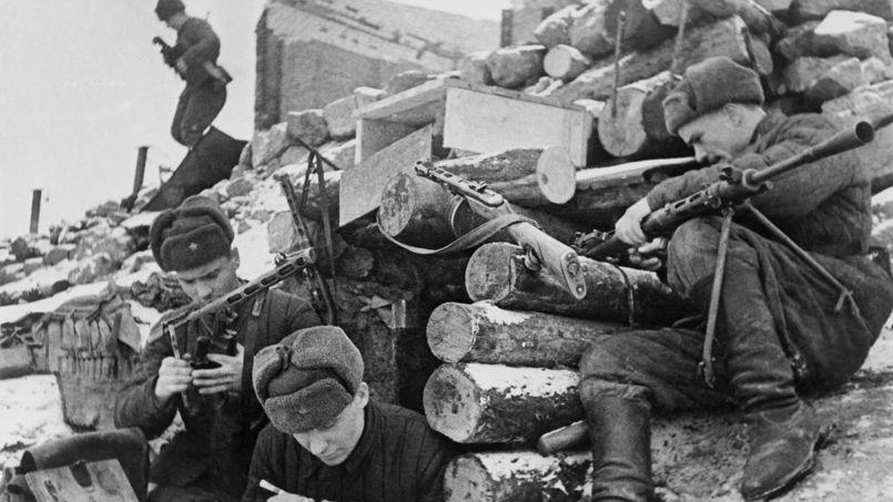 Des soldats soviétiques nettoient leurs armes derrière une position fortifiée, durant la bataille de Stalingrad.