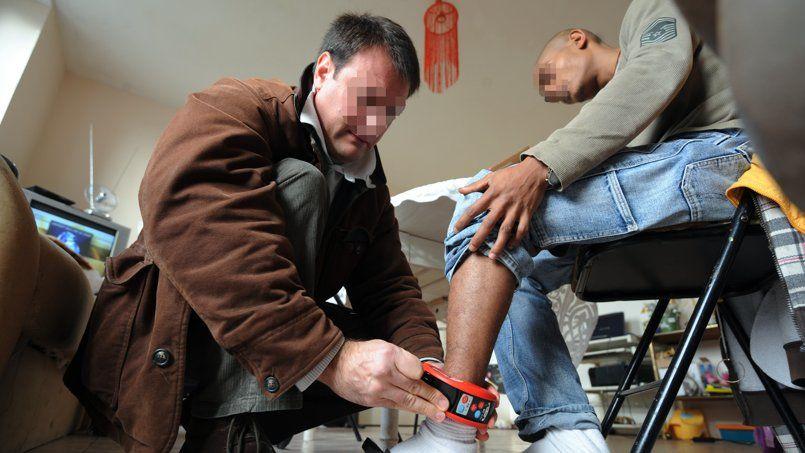 Un surveillant pénitentiaire installe un bracelet électronique à la cheville d'un homme condamné à un placement sous surveillance.