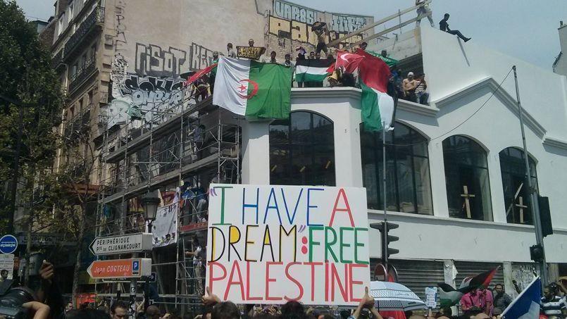 Place Barbès, au début de la manifestation. Sur ce toit, plusieurs drapeaux israéliens ont été brûlés. Crédits photo: Maxime Bellec.