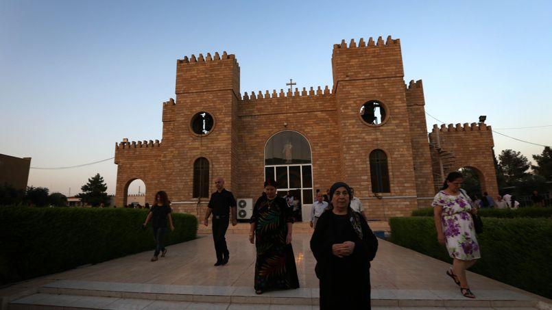 Des fidèles quittent l'église Saint-Joseph après l'office, le 20 juillet 2014 à Erbil. Avant la prise de contrôle de Mossoul par l'Etat islamique, ils étaient près de 35.000 dans cette ville. Aujourd'hui, leur présence ininterrompue depuis près de deux millénaire a pris fin.