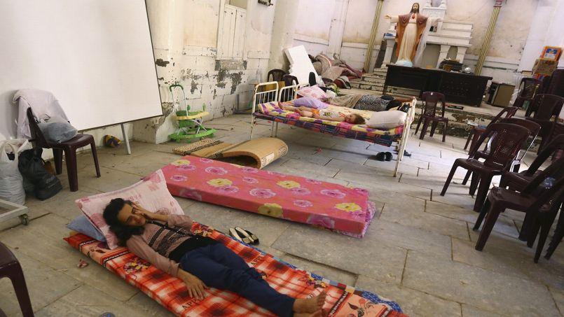 Une famille de chrétiens dorment dans l'église chaldéenne du Sacré Coeur de Jésus, le 20 juillet 2014 à Tel Kaif à 20 km de Mossoul. Les islamistes leur avaient donné jusqu'à samedi midi pour se convertir, payer un impôt islamique, partir ou mourir.