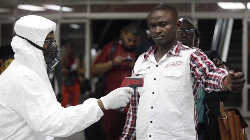 Des agents contrôlent la température de passagers à l'aéroport de Lagos