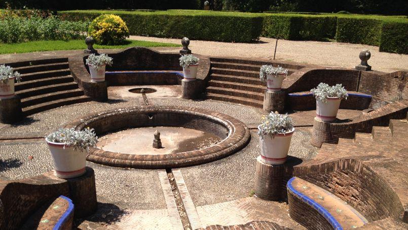 Une disposition de pots en cercle autour d'une fontaine inspirée des plus beaux jardins à la française.