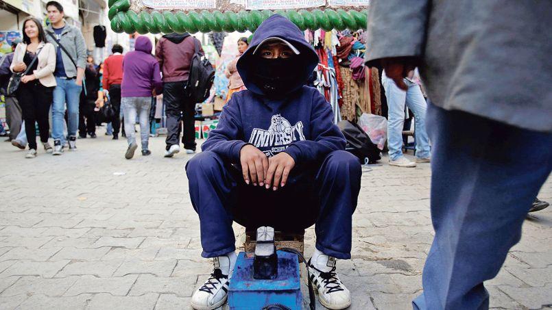 Un garçon travaille comme cireur de chassures dans les rues de La Paz, en Bolivie, en janvier.