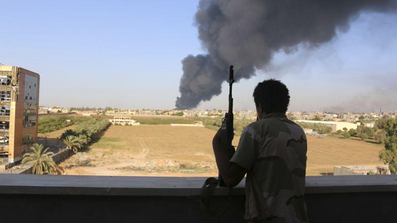 Un membre de la milice de Zintan regarde un réservoir d'essence brûler dans la capitale au début août. Depuis, les islamistes ont pris le contrôle de Tripoli et obligé le gouvernement à s'exiler.