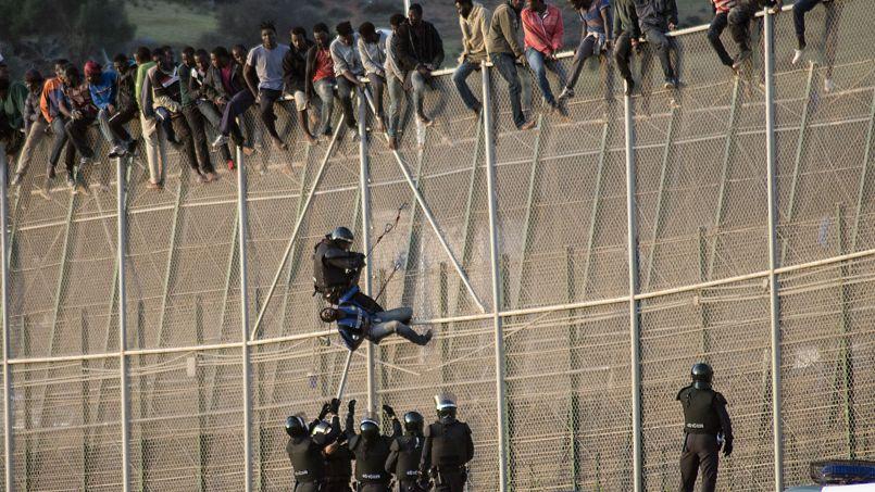 GRAND SAUT. Ce mercredi 15 octobre, un garde civil espagnol vient d'interpeller un migrant africain sur une des clôtures qui séparent le Maroc de l'enclave espagnole de Melilla. Au total, ils plus de 300 illégaux ont tenté de franchir la frontière grillagée haute de plusieurs mètres et certains sont même restés assis sur la barrière pendant de nombreuses heures. Cinq d'entre eux sont parvenus à passer.