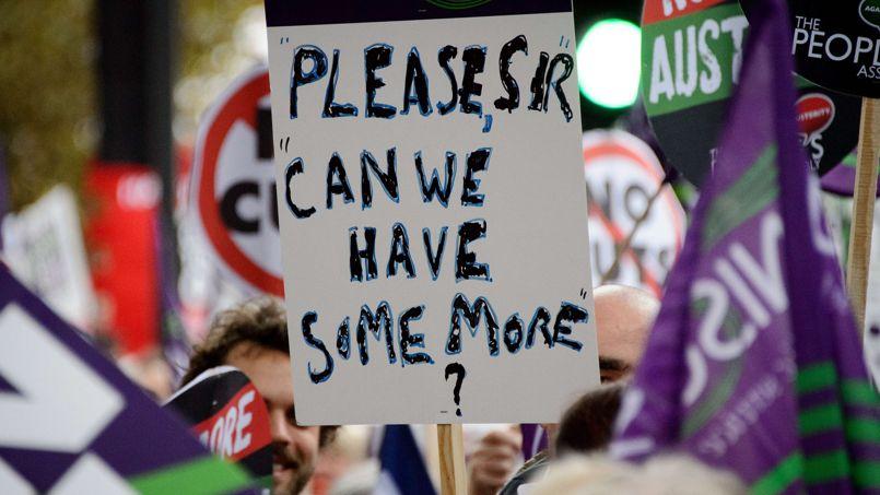 Un homme tient une pancarte où est inscrit «s'il vous plaît, pourrion nous avoir un peu plus?», comme des milliers d'autres manifestants.