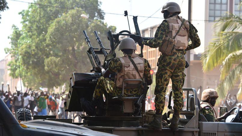 Des soldats burkinabés dans des véhicules blindés font face aux manifestants devant le Parlement.