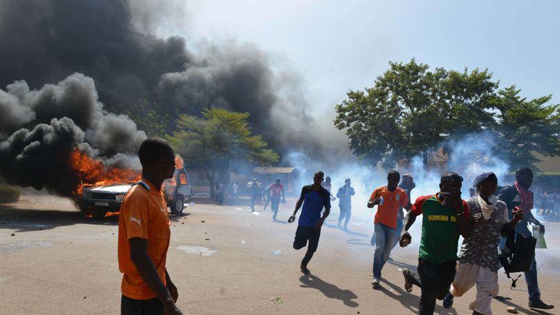 La foule de manifestants se disperse pour échapper aux gaz lacrymogènes tirés par la police aux abords du Parlement.