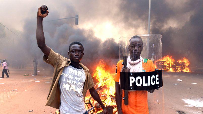 Deux jeunes manifestants posent avec un bouclier de la police en guise de trophée devant les carcasses de voitures incendiées.