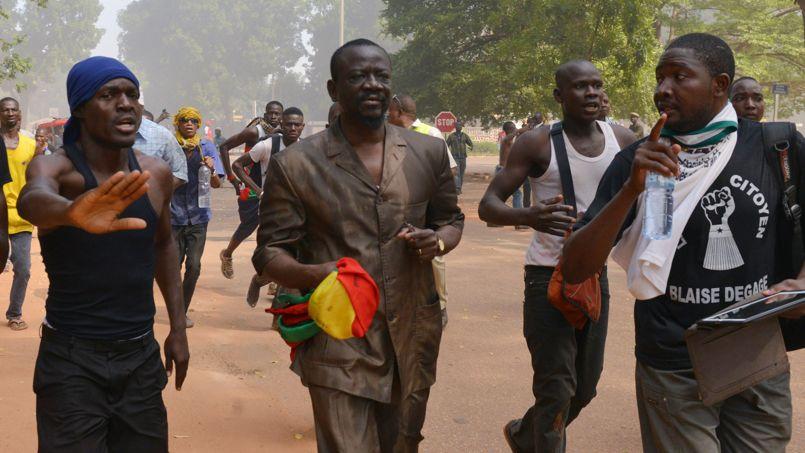 Un député (non identifié) sort du Parlement entouré par deux manifestants anti-gouvernementaux. Mamadou Kadré, un député de l'opposition, a affirmé à l'AFP que ses collègues de la majorité avaient été exfiltrés avant les violences.
