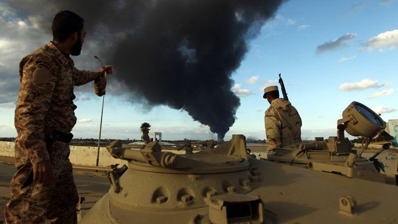 Des soldats fidèles au gouvernement de Tobrouk regardent un incendie provoqué par des combats contre le groupe terroriste Ansar al-Charia dans le port de Benghazi, à l'est du pays.