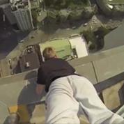 Il fait le poirier en haut d'un gratte-ciel